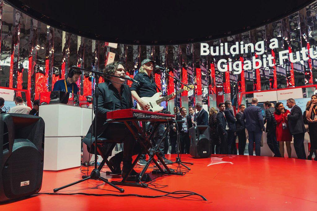 Músicos interpretando una canción en un stand del MWC sincronizados con los de otros stand gracias a la red 5G de Vodafone