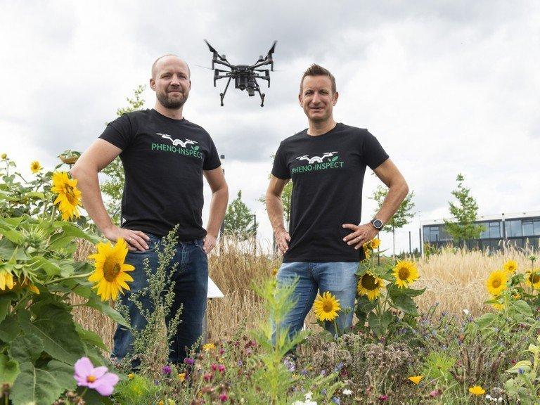 Philipp Lottes (izquierda) y el Prof. Dr. Cyrill Stachniss de la Universidad de Bonn con un dron que registra una vista panorámica de los cultivos. (c) Foto: Barbara Frommann / Uni Bonn